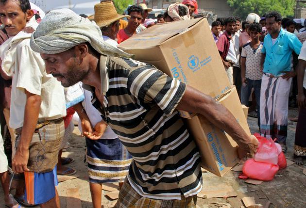 Un homme transporte sur son dos des boites d'aide humanitaire dans la province de Hajjah, au Yémen, le 25 septembre 2018 [ESSA AHMED / AFP/Archives]