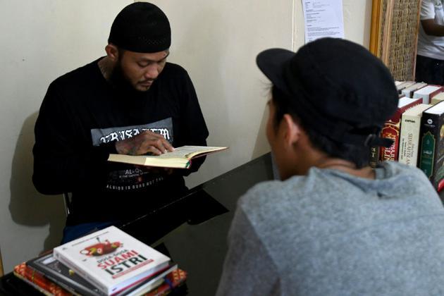 Sandi Widodo fait réciter des versets du Coran à ses clients dans son établissement d'effacement de tatouages, le 18 avril 2018 à Jakarta, en Indonésie [GOH Chai Hin / AFP]