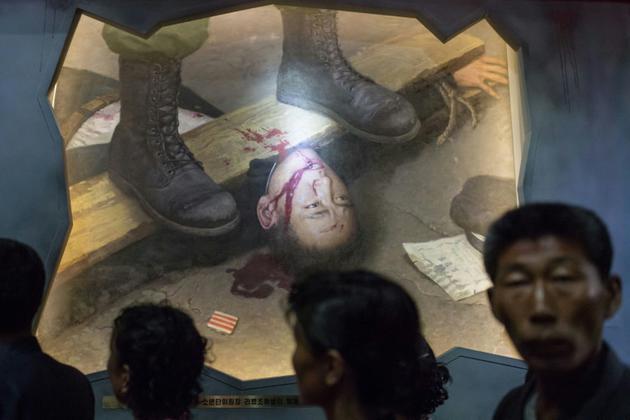 Un groupe de visiteurs passe devant un tableau représentant des soldats américains torturant un Nord-Coréen, le 24 juillet 2017 au Musée des atrocités de guerre américaines à Sinchon, en Corée du Nord [Ed JONES / AFP]
