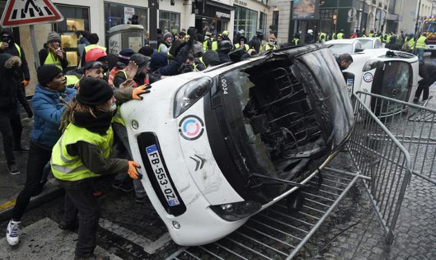 """Destruction d'une voiture pendant la manifestation des """"gilets jaunes"""" près des Champs-Elysées le 1er décembre 2018 [Lucas BARIOULET / AFP/Archives]"""