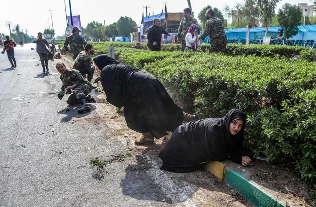 Des femmes et des soldats cherchant à s'abriter lors d'un attentat commis le 22 septembre 2018 pendant un défilé militaire dans la ville iranienne d'Ahvaz [MORTEZA JABERIAN / ISNA/AFP]