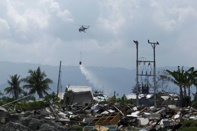 Photographie prise le 18 octobre 2018, à Palu en Indonésie, montrant un hélicoptère pulvériser du désinfectant au dessus de la zone dévastée par un tsunami le 28 septembre [YUSUF WAHIL / AFP/Archives]