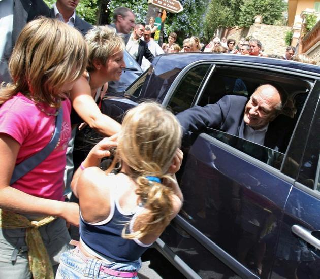 Le président Jacques Chirac salue des personnes le 8 août 2005 après avoir assisté à l'office religieux dominical en l'église de Bormes-les-Mimosas en compagnie de son épouse Bernadette. [ERIC ESTRADE / AFP]