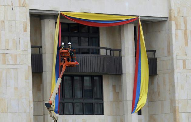 Des ouvriers mettent en place des banderoles aux couleurs du drapeau colombien sur la façade du palais de Justice de Bogota, à la veille de la cérémonie d'investiture du nouveau président, Ivan Duque, le 6 août 2018 [JOHN Vizcaino / AFP]