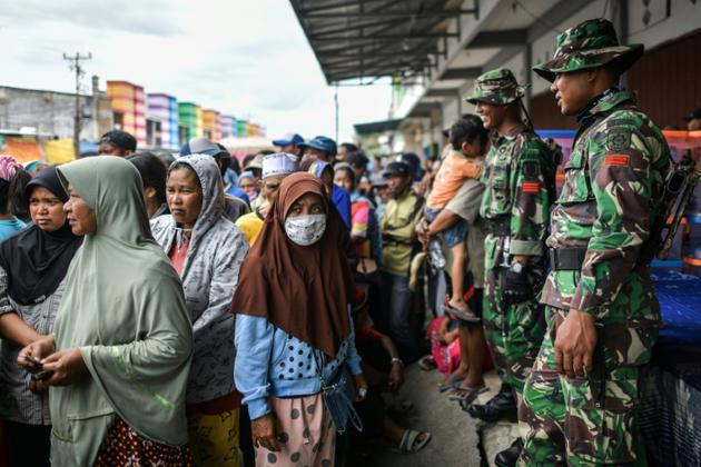 Des habitants de Palu, aux Célèbes, font la queue le 7 octobre 2018 pour recevoir de l'aide après le séisme suivi d'un tsunami qui a ravagé l'île. [MOHD RASFAN / AFP]