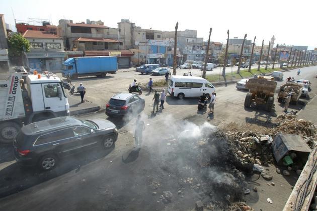 Des volontaires retirent les débris d'une rue menant à l'aéroport international de Beyrouth, après des manifestations, le 19 octobre 2019   [IBRAHIM AMRO / AFP]