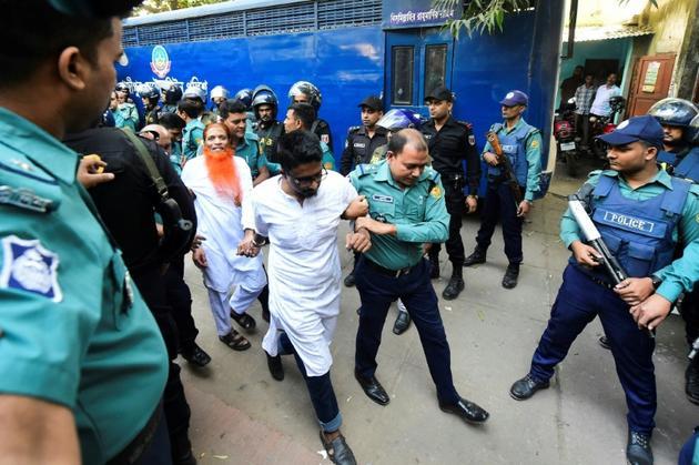 Des policiers escortent des détenus lors du procès le 27 novembre 2019 d'islamistes radicaux accusés pour l'attaque d'un café de Dacca, dans lequelle 22 personnes dont 18 étrangers avaient perdu la vie. [Munir UZ ZAMAN / AFP]