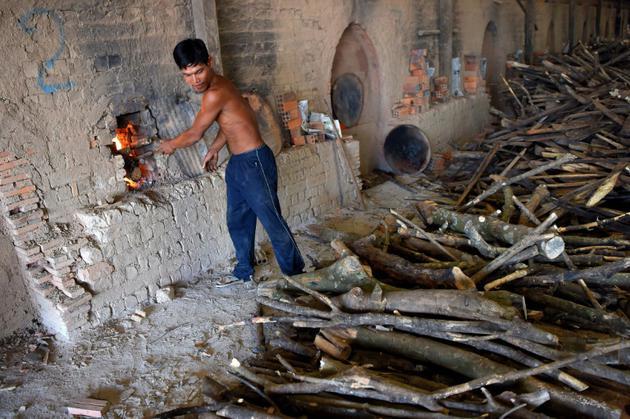 Un Cambodgien travaille dans une manufacture de briques près de Phnom Penh, le 11 décembre  2018 [TANG CHHIN Sothy / AFP]