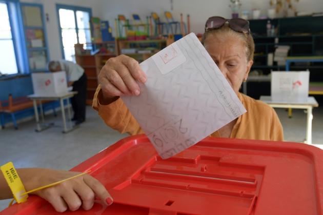 Une Tunisienne glisse son bulletin dans l'urne, lors des législatives, le 6 octobre 2019 à Tunis [FETHI BELAID / AFP]