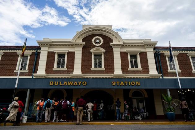 """Des Zimbabwéens achètent des billets pour monter à bord du """"train de la liberté, le 28 janvier 2019 à Bulawayo [ZINYANGE AUNTONY / AFP]"""