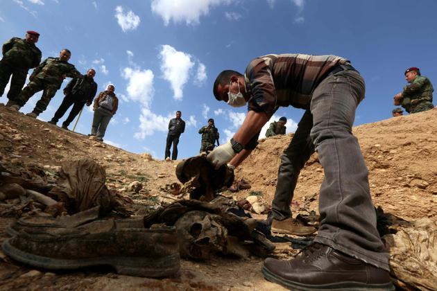 Des membres de la minorité yazidie en Irak cherchent des preuves pouvant leur permettre de retrouver des proches disparus ou tués par le groupe Etat islamique (EI), dans un charnier près du village de Sinuni, dans la région de Sinjar (nord-ouest), le 3 février 2015 [Safin HAMED / AFP/Archives]