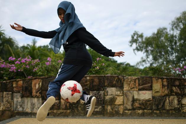 Qhouirunnisa' Endang Wahyudi, 18 ans, fait une figure de football freestyle, dans un parc à Klang, près de Kuala Lumpur le 11 juillet 2018 [MOHD RASFAN / AFP]