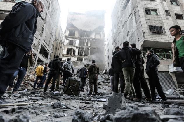 Des Palestiniens se rassemblent sur le site d'un immeuble en ruines après des frappes aériennes israéliennes, le 13 novembre 2018 dans la bande de Gaza [MAHMUD HAMS / AFP]