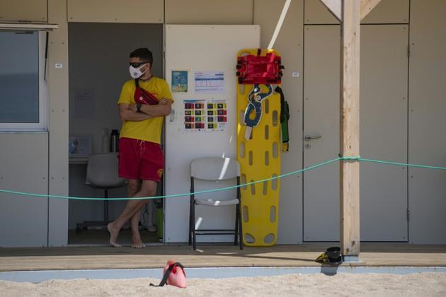 Un secouriste porte un masque de protection et surveille la plage de Lloret de Mar, le 22 juin 2020 en Espagne [Josep LAGO / AFP]