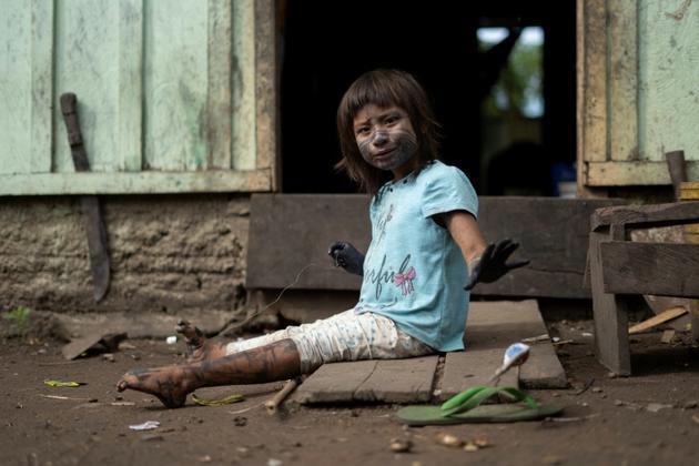 Une fillette indigène Arara devant sa maison dans un camp de la tribu Laranjal en Amazonie brésilienne, le 15 mars 2019 [Mauro Pimentel / AFP]