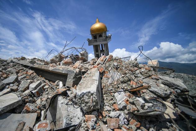 Une partie d'une mosquée effondrée surgit des décombres laissés par un puissant séisme suivi d'un tsunami dans le quartier de Perumnas Balaroa à Palu, sur l'île des Célèbes en Indonésie, le 6 octobre 2018 [MOHD RASFAN / AFP]