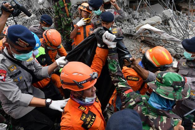 Des secouristes transportent le 8 août 2018 à Bangsal la dépouille d'une victime d'un séisme meurtrier en Indonésie [ADEK BERRY / AFP]