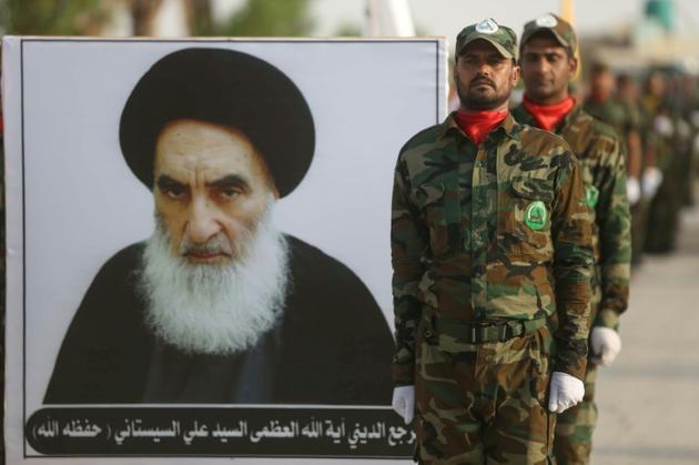 Des miliciens irakiens du groupe Liwa al-Toufouf photographiés près d'un portrait du grand ayatollah Ali Sistani, plus grande autorité chiite d'Irak, à Kerbala le 30 août 2019 [ / AFP/Archives]
