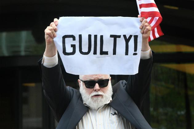"""Un manifestant tient à bout de bras une pancarte """"coupable"""" devant le tribunal d'Alexandria en Virginie où l'ex-chef de campagne de Donald Trump a été reconnu coupable de fraude bancaire et fiscale, le 21 août 2018   [Jim WATSON / AFP]"""