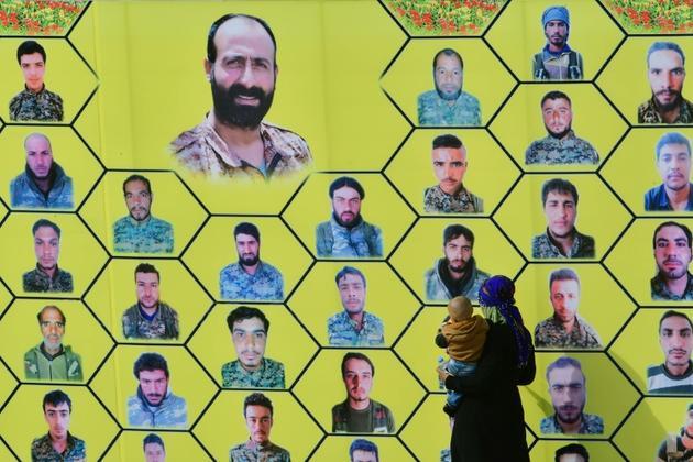 Une femme et son enfant regardent une grande pancarte montrant les visages des combattants des Forces démocratiques syriennes tués lors de combats contre le groupe Etat islamique, le 23 mars 2019 près du champ pétrolier d'Al-Omar [GIUSEPPE CACACE / AFP]