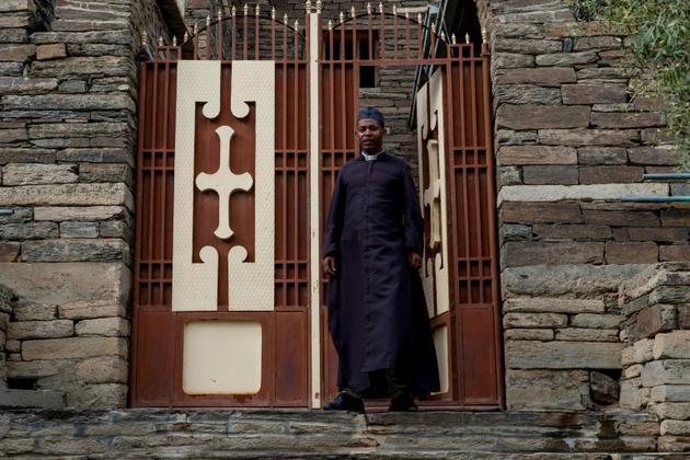 Le père Daniel Hagos devant son église d'Alitena, à la frontière érythréo-éthiopienne, le 12 juillet 2018.<br />  [Maheder HAILESELASSIE TADESE / AFP]
