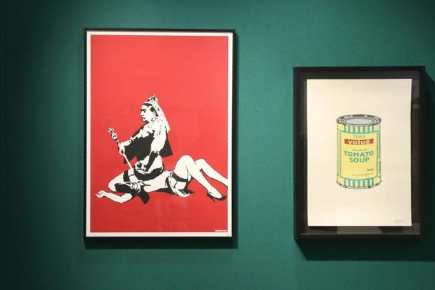 """Les œuvres """"Queen Vic"""" et """"Soup can yellow"""" réalisées par l'artiste britannique Banksy exposées à la vente chez Artcurial à Paris, le 24 octobre 2018 [JACQUES DEMARTHON / AFP]"""