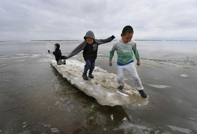 Des enfants jouent sur un morceau de glace près du village eskimau de Yupik, en Alaska (Etats-Unis), le 19 avril 2019 [Mark RALSTON / AFP/Archives]