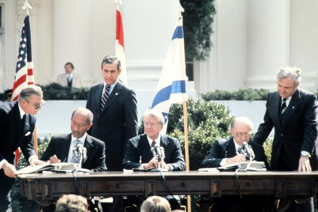 Anouar al-Sadate (à gauche) et Menachem Begin (à droite) signent le traité de Washington en présence de Jimmy Carter (au centre) le 26 mars 1979  [- / FILES-CONSOLIDATED NEWS PICTURES/AFP]