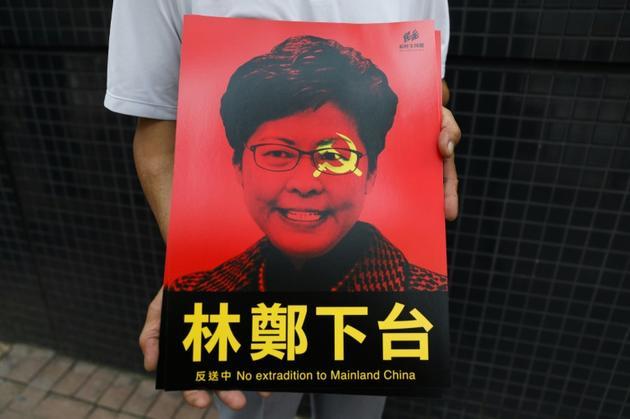 La cheffe de l'exécutif hongkongais, Carrie Lam, représentée sur une affiche tenue par un participant à la manifestation contre un projet de loi d'extradition, le 9 juin 2019 [DALE DE LA REY / AFP]