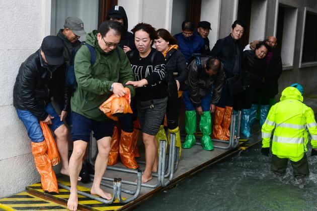Des touristes marchent sur un passerelle à Venise le 29 octobre 2018<br />  [Miguel MEDINA / AFP]