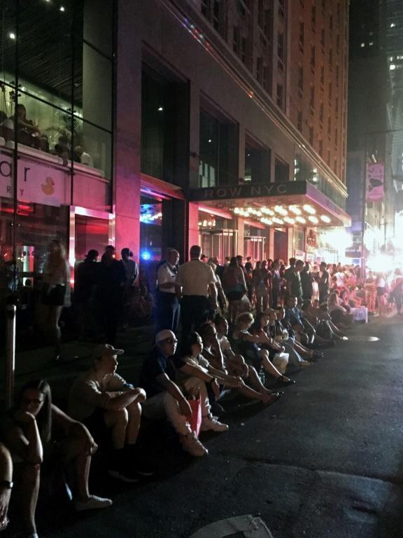 Des clients de l'hôtel Row NYC à Manhattan attendent sur le trottoir après une panne d'électricité géante [Thomas URBAIN / AFP]