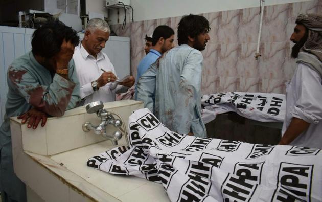Des personnes venues identifier les corps de proches, le 13 juillet 2018 à Quetta, après un attentat suicide qui a frappé une réunion électorale à Mastung, au sud-ouest du Pakistan<br />  [BANARAS KHAN / AFP]
