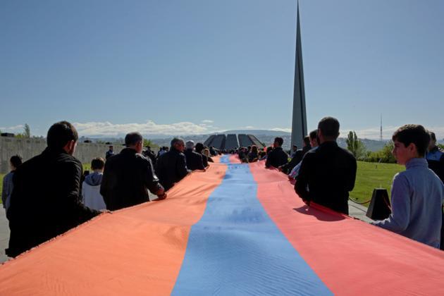 Des Arméniens portant un drapeau national géant participent aux commémorations du génocide arménien, mardi 24 avril 2018 à Erevan [KAREN MINASYAN / AFP]