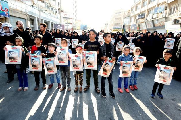 Des enfants iraniens brandissent le portrait d'une des victimes de l'attentat commis à Ahvaz, dans le sud-ouest de l'Iran, à l'occasion des funérailles organisées le 24 septembre 2018 [ATTA KENARE / AFP]