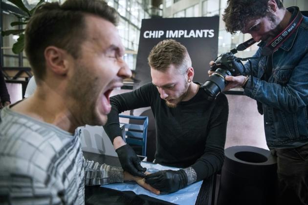 Un homme réagit alors qu'un autre insère un implant sous sa peau, à Stockholm, le 18 janvier 2018 [Jonathan NACKSTRAND / AFP]