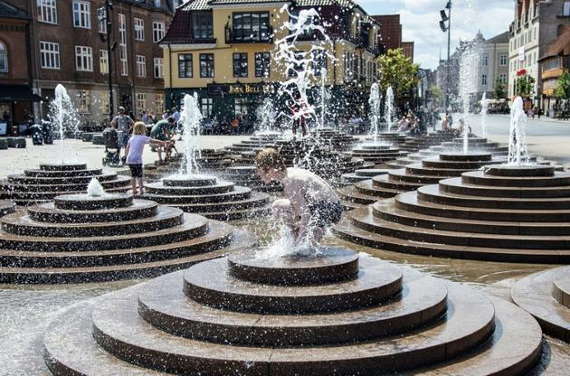 Des habitants se rafraichissent dans les fontaines de la Toldbod Plads à Aalborg, au Danemark, le 24 juillet 2019 [Henning Bagger / Ritzau Scanpix/AFP]
