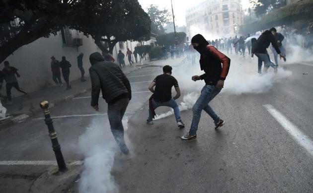 Des manifestants face à des tirs de lacrymogène à Alger, le 22 février 2019 [RYAD KRAMDI                         / AFP]