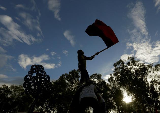Un partisan du président nicaraguayen Daniel Ortega agite un drapeau du Front sandiniste de libération nationale (FSLN), pendant un rassemblement à Managua, le 15 août 2018 [INTI OCON / AFP]
