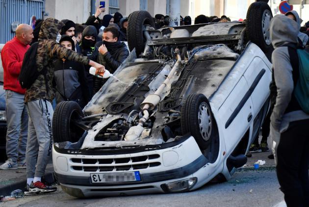Un jeune asperge de liquide inflammable une voiture renversée lors d'une manifestation de lycéens, le 6 décembre 2018 à Marseille [GERARD JULIEN / AFP]