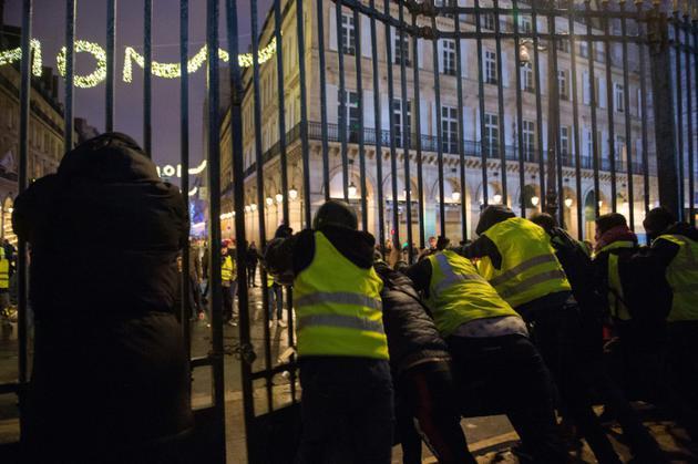 Manifestants portant un gilet jaune, poussant les grilles du jardin des Tuileries, à Paris le 1er décembre 2018 [- / AFP]