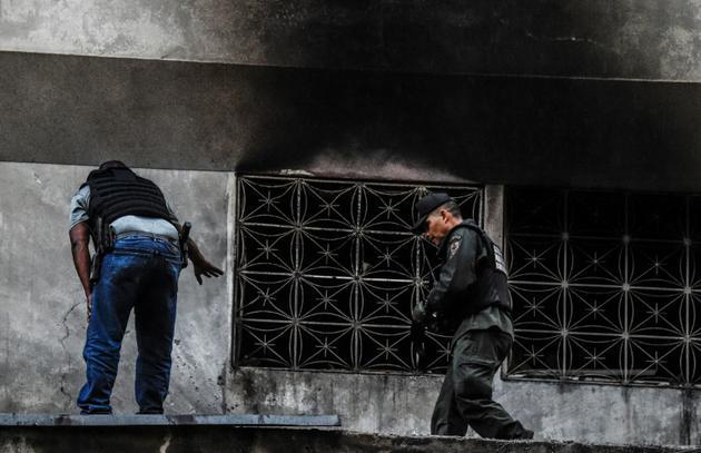 Des membres des forces de sécurité inspectent un immeuble après une tentative d'attentat contre le président vénézuélien Nicolas Maduro, le 5 août 2018 à Caracas [Juan BARRETO / AFP]