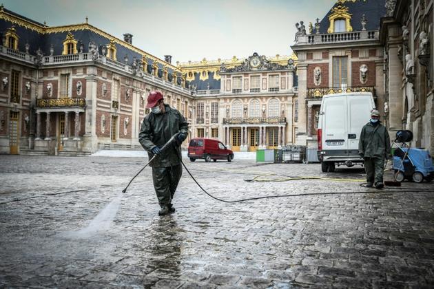 Des employés nettoient la cour d'honneur du château de Versailles le 5 juin 2020 [STEPHANE DE SAKUTIN / AFP]