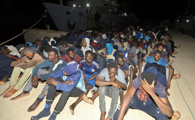 Des migrants secourus en Méditerranée le 24 juin 2018 attendent à une base navale à Tripoli [MAHMUD TURKIA / AFP]