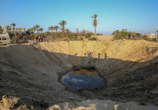 Des Palestiniens marchent autour d'un cratère creusé par une frappe israélienne, dans le sud de la bande de Gaza, le 2 novembre 2019 [SAID KHATIB / AFP]