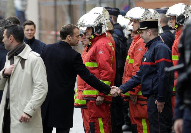 """Le président Macron salue les pompiers et gendarmes lors de sa visite dans les rues de Paris, le 2 décembre 2018 au lendemain des manifestations des """"gilets jaunes"""" [Geoffroy VAN DER HASSELT / AFP]"""