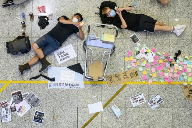 Des manifestants prodémocratie se reposent lors d'une manifestation à l'aéroport international de Hong Kong le 12 août 2019 [Philip FONG / AFP]
