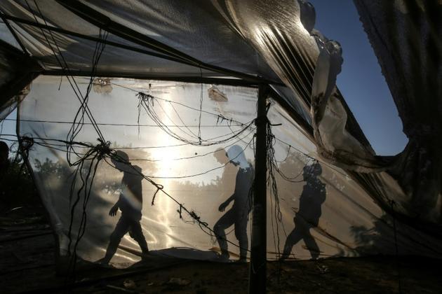 Des Palestiniens passent derrière une serre endommagée par une frappe israélienne, dans le sud de la bande de Gaza, le 2 novembre 2019 [SAID KHATIB / AFP]