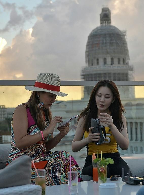 Des touristes asiatiques sur le toit de l'hôtel Gran Manzana à La Havane, le 11 février 2019 [Yamil LAGE / AFP]