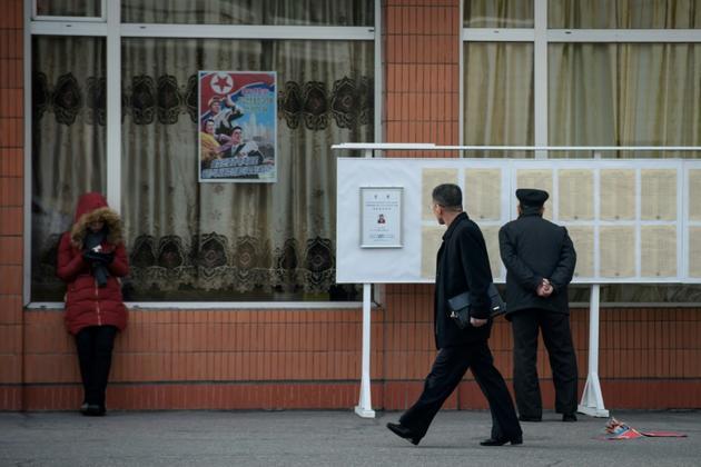 Des passants devant des listes électorales, le 9 mars 2019 à Pyongyang [Ed JONES / AFP]