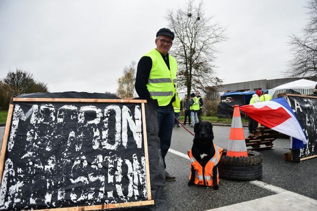 """Un manifestant """"gilet jaune"""" avec son chien devant un écriteau portant l'inscription """"Macron démission"""", le 2 décembre 2018 à Torce, près de Rennes, dans l'ouest de la France.<br /> [JEAN-FRANCOIS MONIER              / AFP/Archives]"""